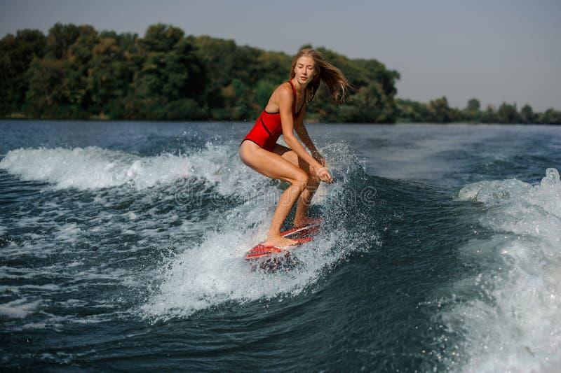 Девушка в купальнике на борту в море стоковые фото