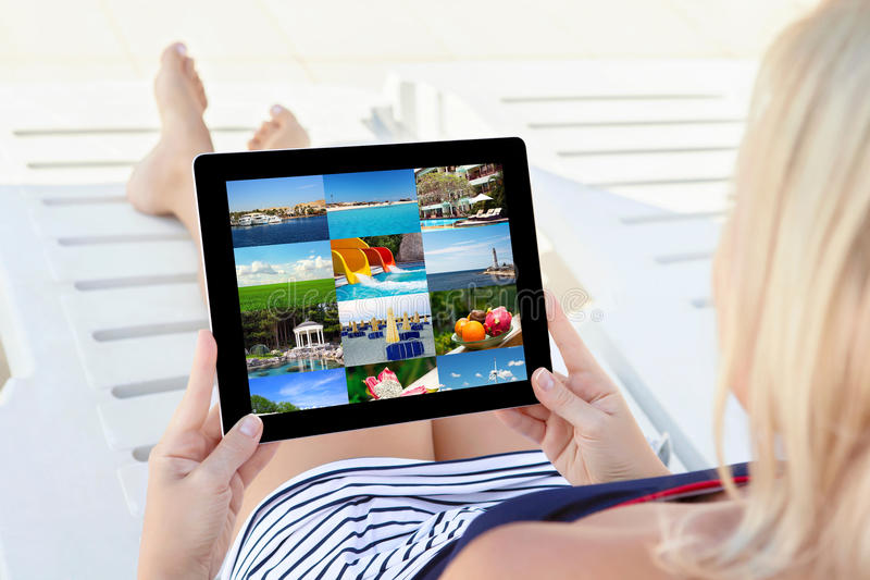 Девушка в купальном костюме лежащ на салоне фаэтона с таблеткой стоковое изображение