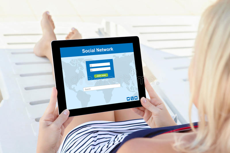 Девушка в купальном костюме с таблеткой компьютера и социальной сетью стоковое фото rf