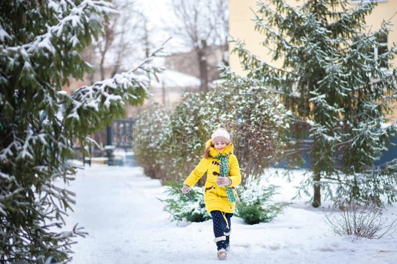 Девушка в куртке в зиме радуется в снеге, скачках, снежных комьях ходов, бегах в зиме Holid зимы детей стоковое фото rf