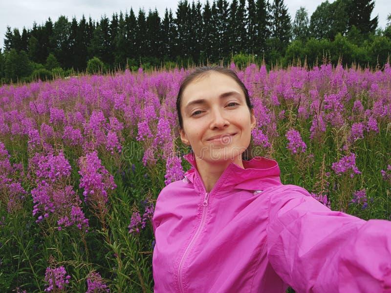 Девушка в куртке спорт пурпура делает selfie в красивом ярком поле Иван-чая во время цвести Весна, природа, утеха стоковая фотография