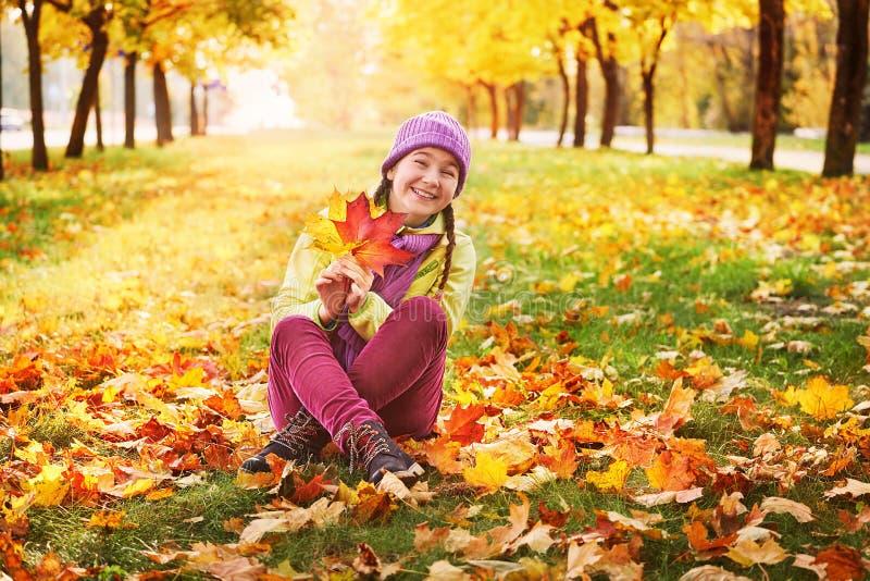 Девушка в листьях осени в парке в свежем воздухе стоковые изображения rf