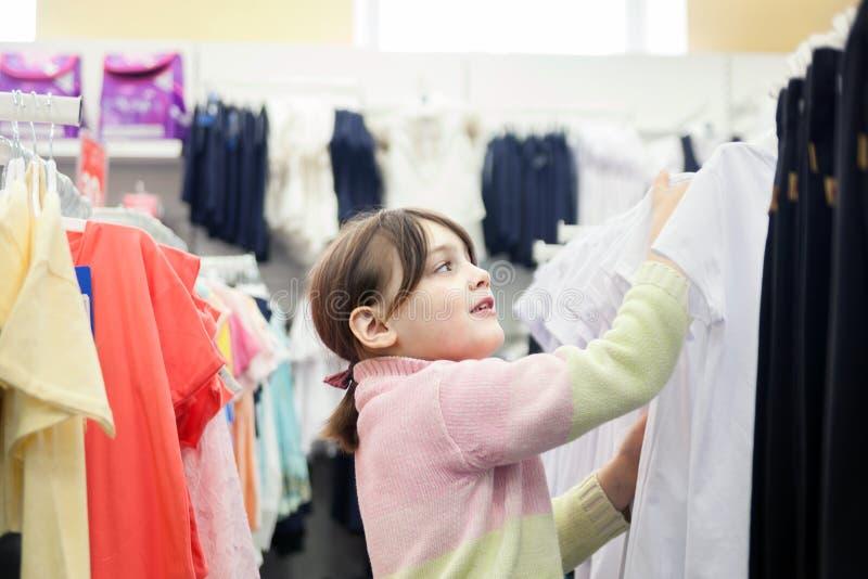Девушка в магазине одежды ` s детей стоковое изображение rf