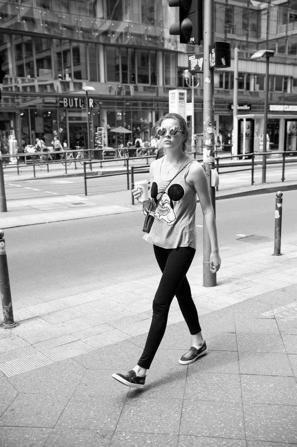 Девушка в модных одеждах и солнечных очках идя на мостоваую стоковая фотография