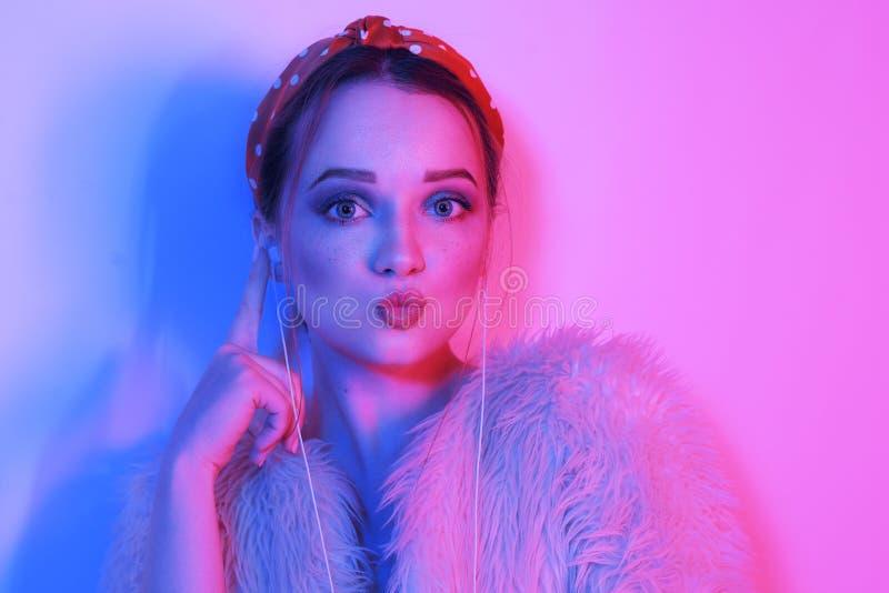 Девушка в наушниках слушая музыку Улыбки и смех девушки Портрет моды молодой элегантной девушки в розовом пальто и стоковые изображения rf