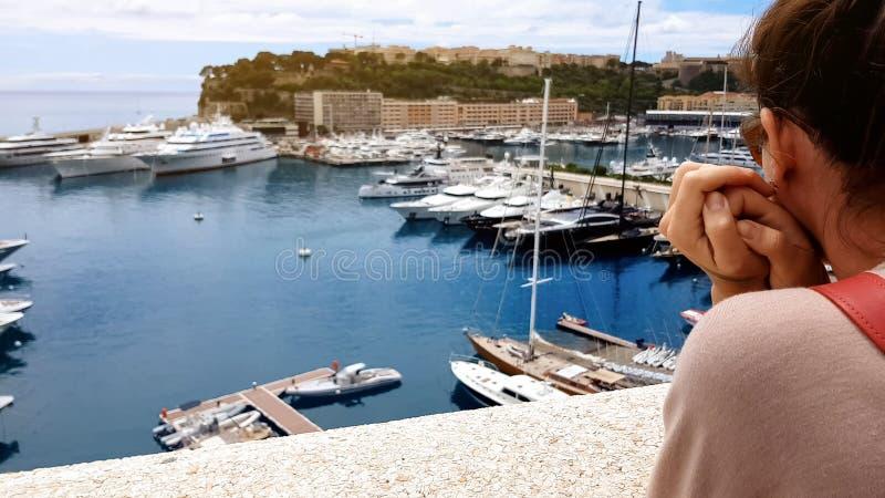 Девушка в несенных одеждах смотря дорогой корабль, зазор между богачами и бедные стоковое изображение