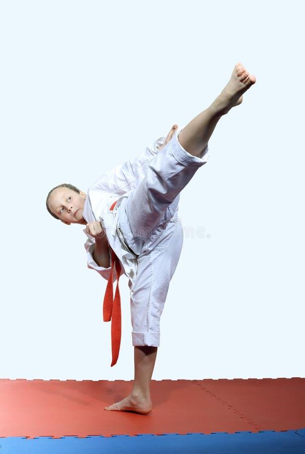 Девушка в ноге пинком локомотивного депо ударов karategi стоковая фотография rf