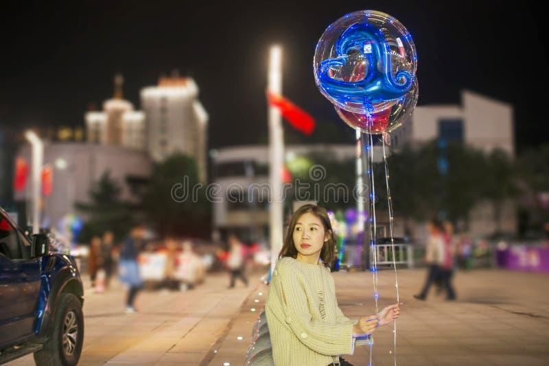 Девушка в ноче улиц фестиваля держа воздушный шар стоковая фотография