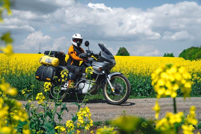 Девушка в обмундировании и стеклах защиты с touristic мотоциклом Поле цветков рапса желтое на предпосылке Путешествие следа прикл стоковые фотографии rf