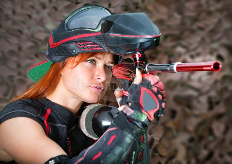 Девушка в обмундировании пейнтбола принимая цель с оружием стоковое изображение