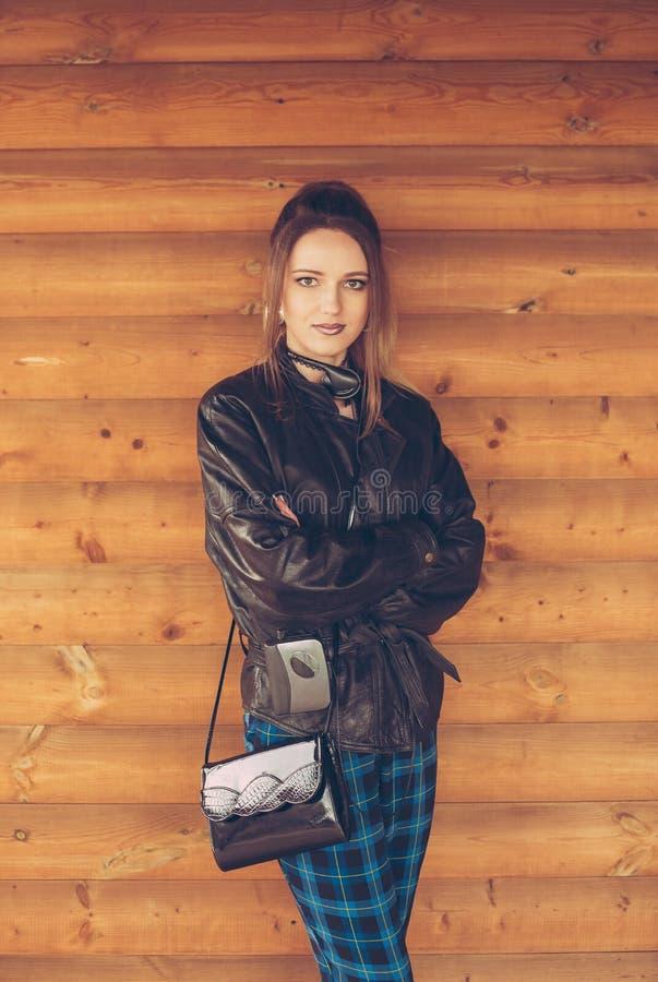 Девушка в одеждах девяностых годов, на предпосылке деревянной стены стоковая фотография rf