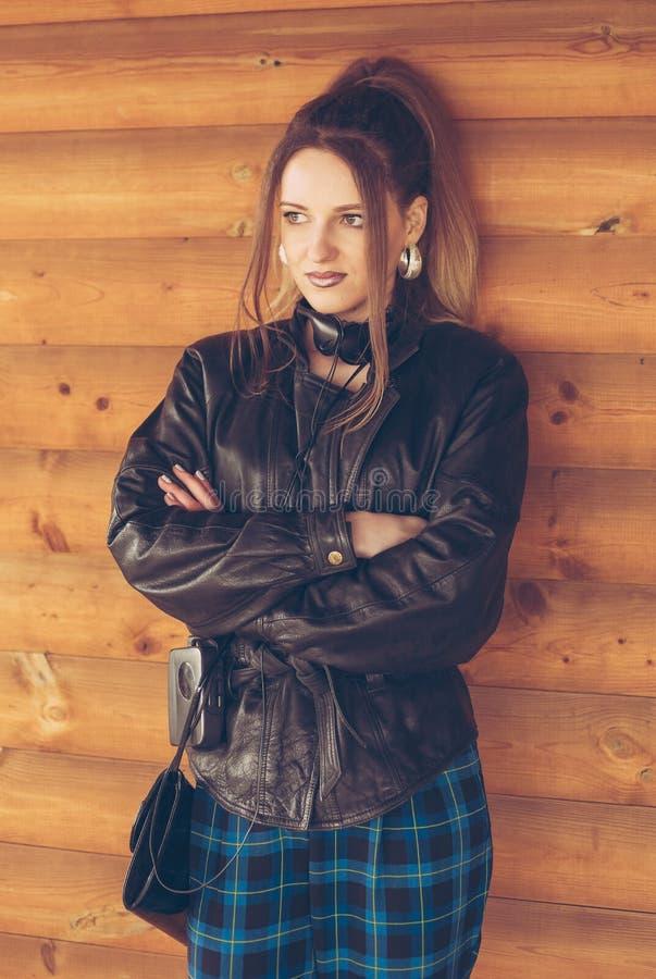 Девушка в одеждах девяностых годов, на предпосылке деревянной стены стоковое изображение rf