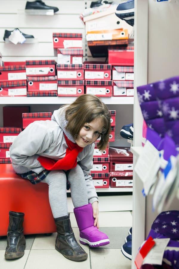 Девушка в одеждах зимы пробуя теплые ботинки стоковое фото