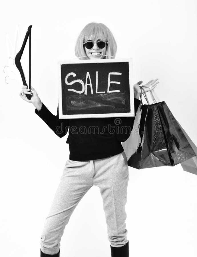 Девушка в пакете удерживания парика, вешалках, доске с надписью продажи стоковое фото