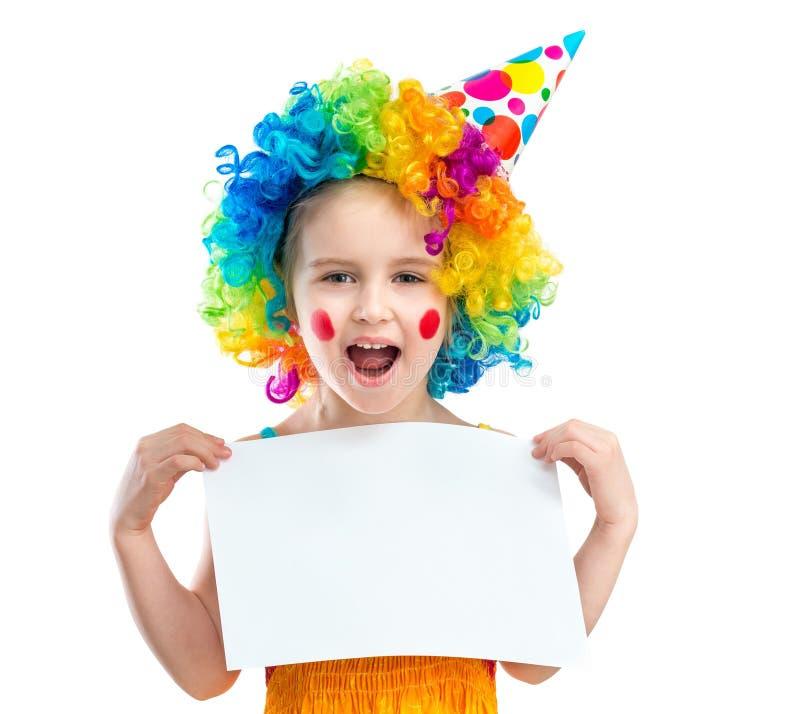 Девушка в парике клоуна держит чистый лист бумаги, изолированный на белой предпосылке стоковые фото