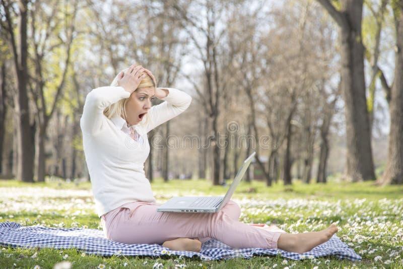 Девушка в парке весной с ее компьтер-книжкой стоковое фото