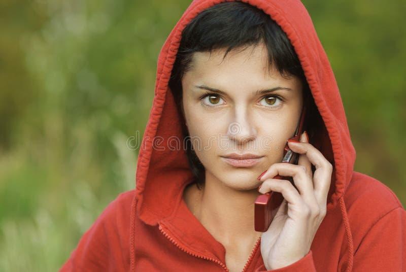 Девушка в парке говорит телефоном стоковые изображения rf