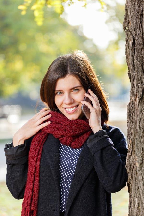 Девушка в парке осени деревом, говорит телефоном стоковые изображения