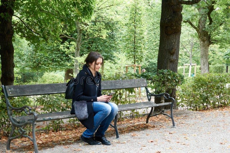 Девушка в парке сидит самостоятельно на стенде с телефоном стоковое изображение