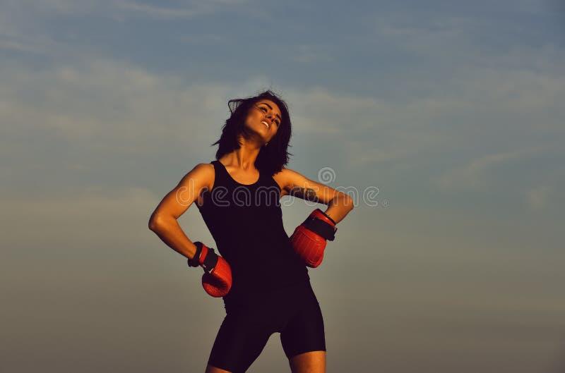 Девушка в перчатке бокса на предпосылке голубого неба, пинке силы стоковая фотография rf