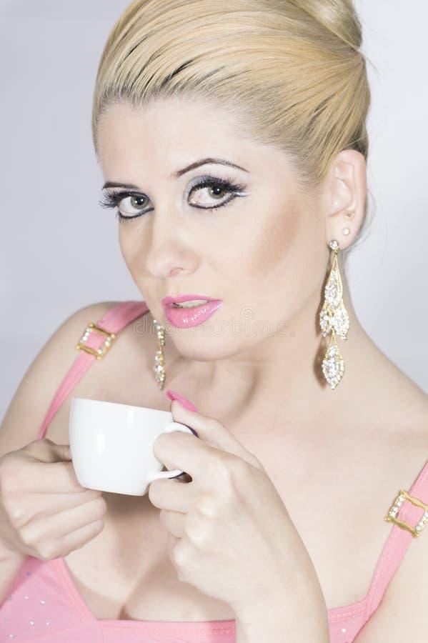 Девушка в пинке с чашкой кофе стоковое фото