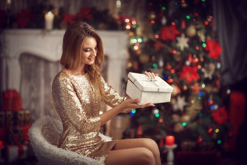 Девушка в платье золота с подарком в коробке стоковое изображение
