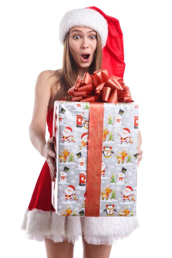 Девушка в платье рождества, при удивленный взгляд держа огромную подарочную коробку белизна изолированная предпосылкой стоковое изображение rf