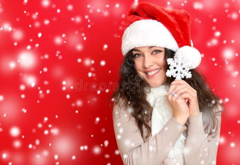Девушка в портрете шляпы santa при большая игрушка снежинки представляя на предпосылке красного цвета, концепции праздника рождес стоковая фотография