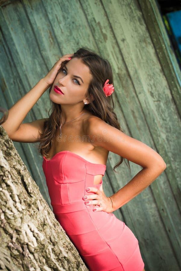 Девушка в положении barrette платья и цветка коралла стоковая фотография