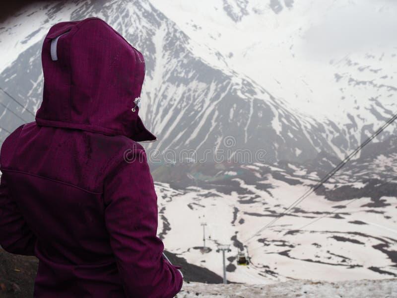 Девушка в пурпурной куртке смотрит горы покрытые со снегом стоковое изображение rf