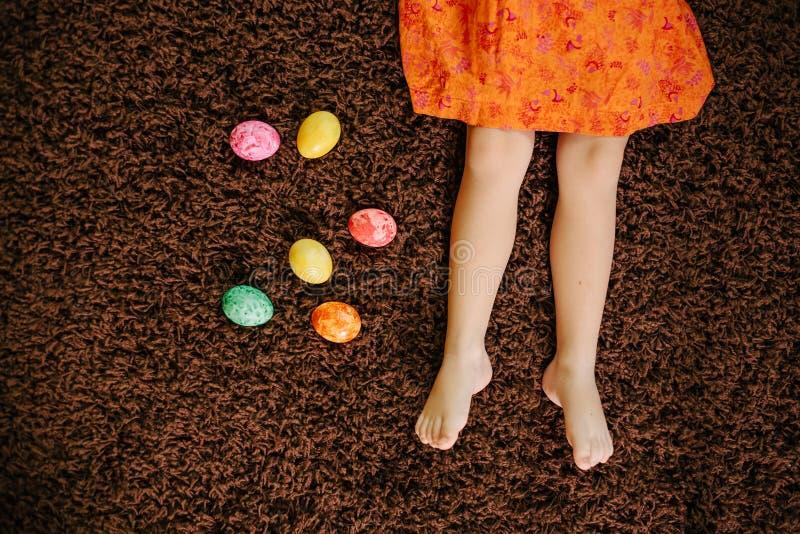 Девушка в платье лежит около пасхальных яя Ноги стоковые изображения
