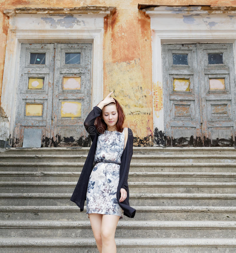 Девушка в платье на лестницах здания стоковые фотографии rf