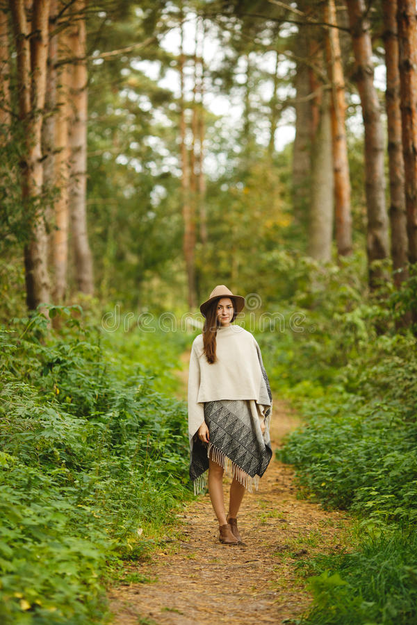 Девушка в плащпалате и шляпе в лесе стоковое изображение
