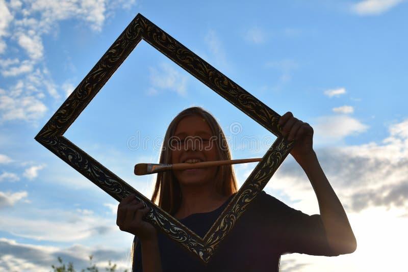 Девушка в рамке искусства outdoors Художник рисует портрет девушки Инструменты и аксессуары художника стоковое изображение rf