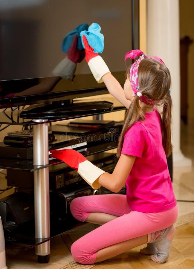 Девушка в резиновых перчатках очищая экран ТВ от пыли с тканью стоковая фотография