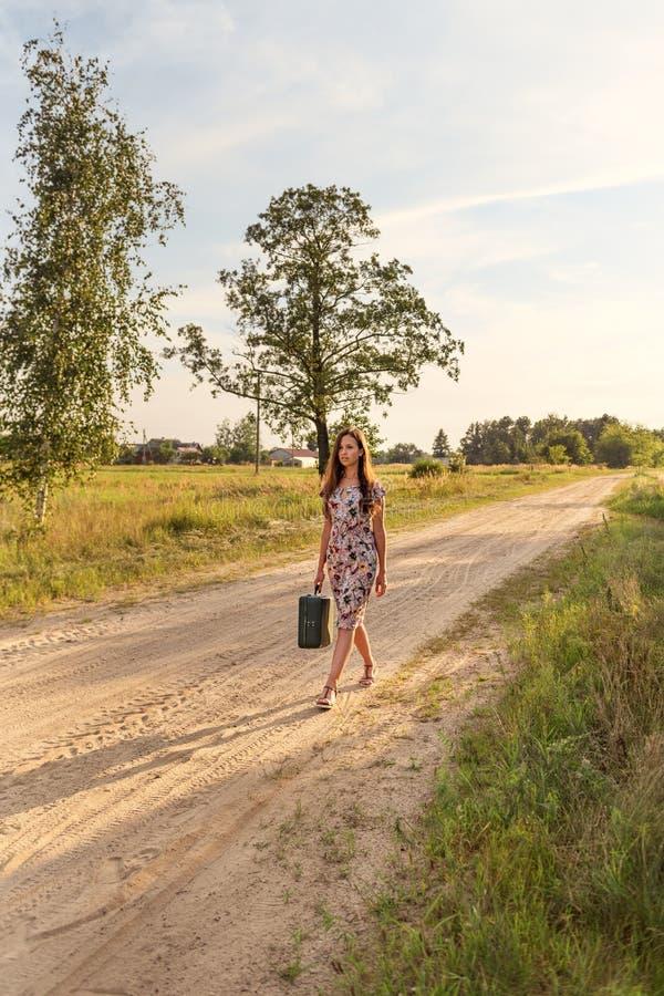 Девушка в ретро винтажном платье с чемоданом и длинными пропуская волосами идет вдоль дороги в желтых лучах солнечного света стоковые фото