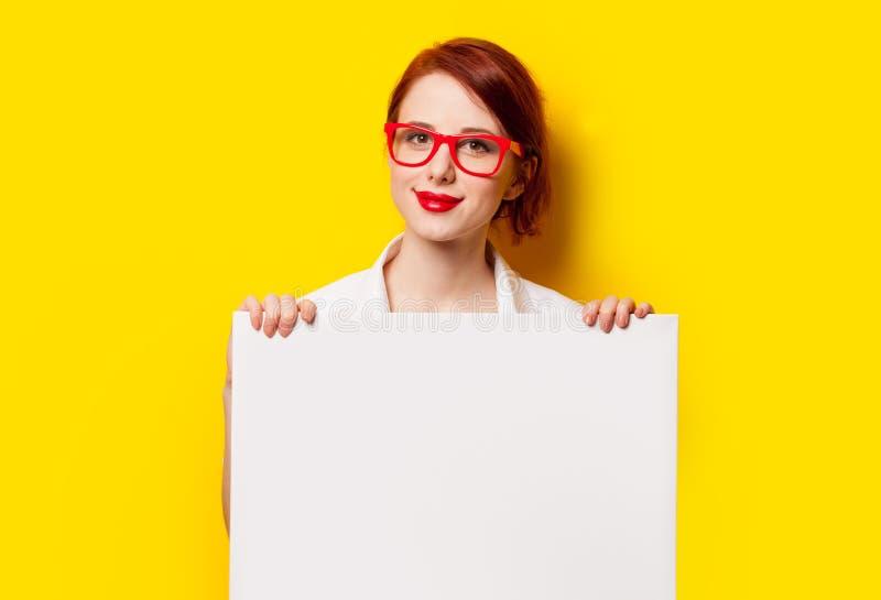 Девушка в рубашке и стеклах с белой доской стоковая фотография