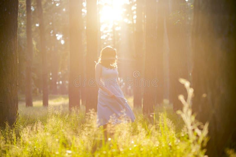 Девушка в светлом - голубое платье в солнце в середине леса стоковое фото rf