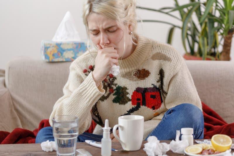 Девушка в свитере кашляет, сидя на диване Колды и грипп Пациент простудился, чувствуя себя больным и кашляя в стоковые изображения rf