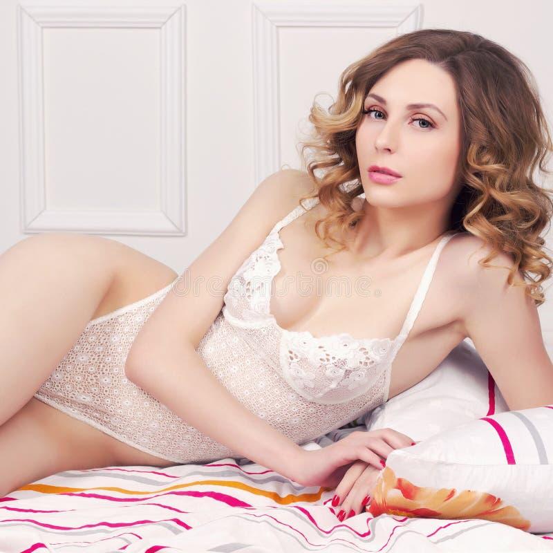 Девушка в сексуальном нижнем белье в кровати стоковые фотографии rf