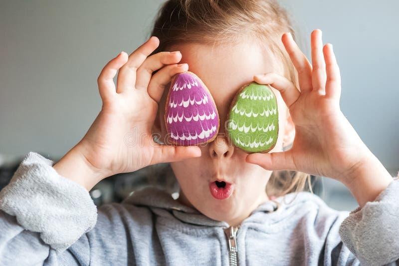 Девушка в серой доле держа пряник пасхи в форме яя в ее конце-вверх рук Ребенок закрывает его глаза с поваром стоковое фото