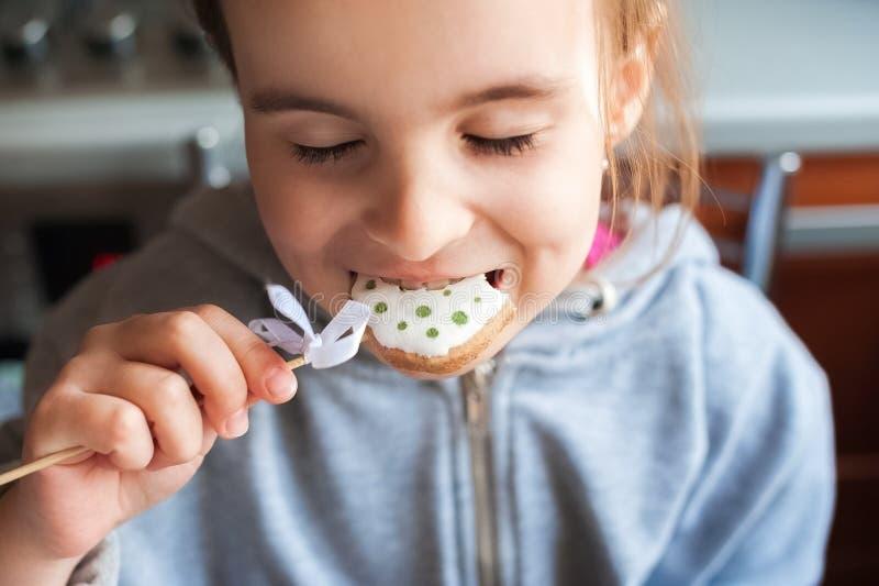 Девушка в серой заплате свитера держит пасхальное яйцо на ее палочке в ее руке Маленькая девочка есть cl печенья имбиря зайчика п стоковая фотография