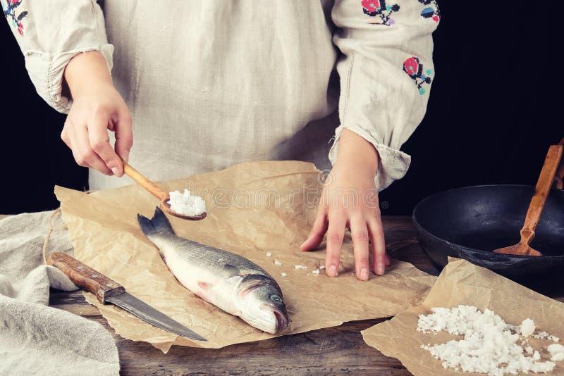 девушка в сером длинном платье белья держит полную ложку соли стоковые изображения
