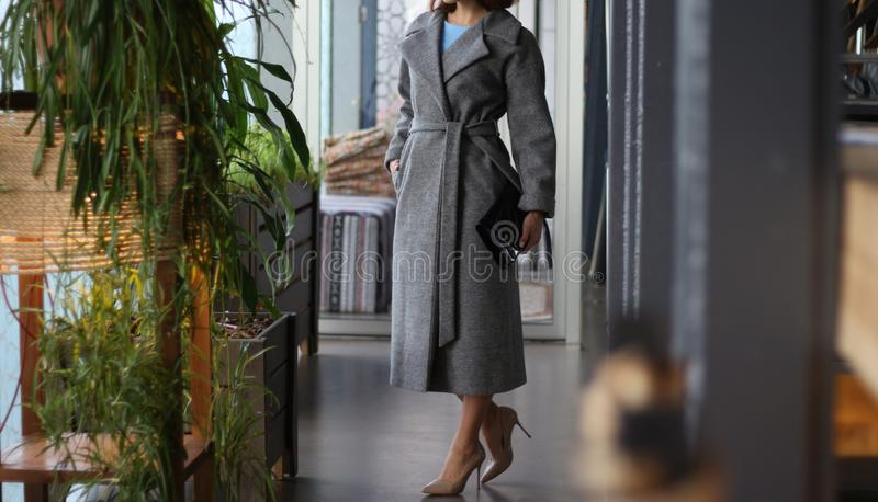Девушка в сером пальто и бежевых ботинках, с черной сумкой, стоит в коридоре кафа, гостиницы, ресторана, около зеленого flowe стоковая фотография rf