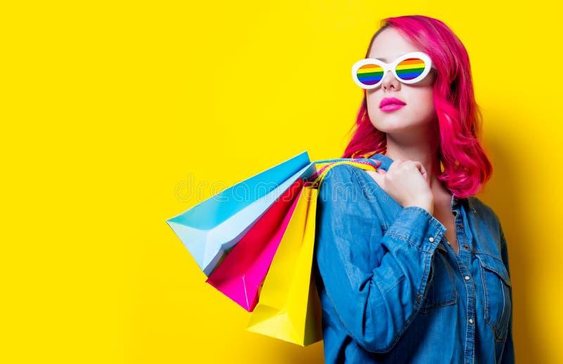 Девушка в солнечных очках радуги держащ сумки стоковое изображение rf