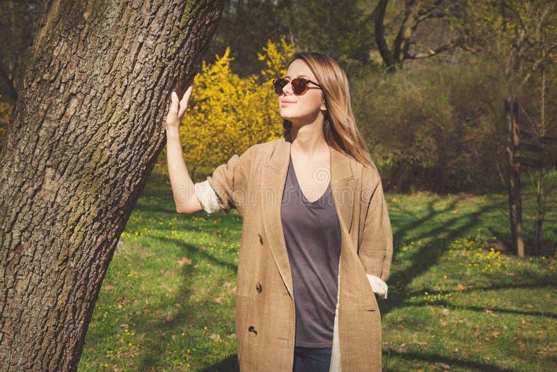 Девушка в солнечных очках стоя около дерева стоковые изображения rf