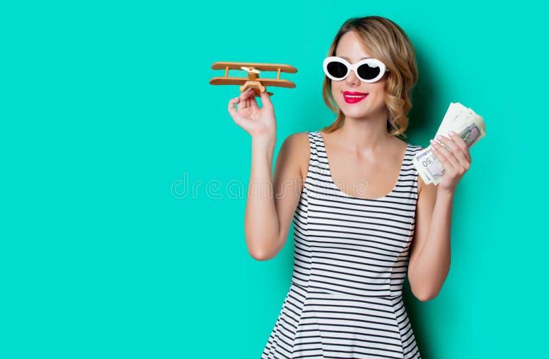 Девушка в солнечных очках с деньгами и деревянным самолетом стоковое фото rf