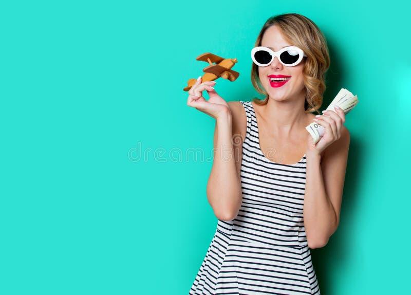 Девушка в солнечных очках с деньгами и деревянным самолетом стоковое фото