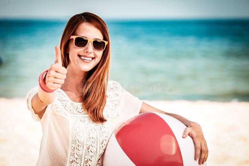Девушка в солнечных очках с ОК шоу шарика пляжа стоковые изображения rf