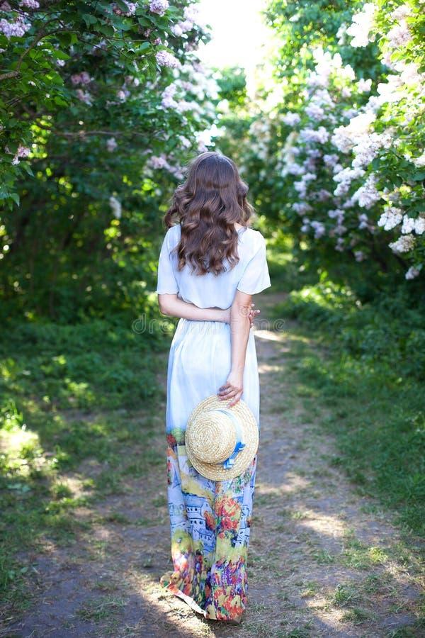 Девушка в соломенной шляпе с голубой лентой на после полудня весны E Ультрамодное случайное обмундирование лета или весны Мода ул стоковое фото